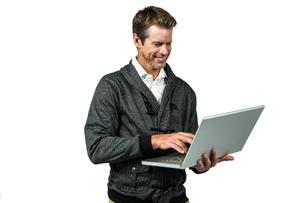 Cheerful man using laptopの写真素材 [FYI00010205]