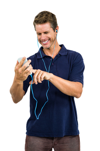 Cheerful man listening music while using mobile phoneの写真素材 [FYI00010214]