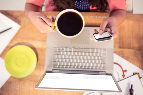 Cropped image of businesswoman using phone while holding coffee cupの写真素材 [FYI00010266]