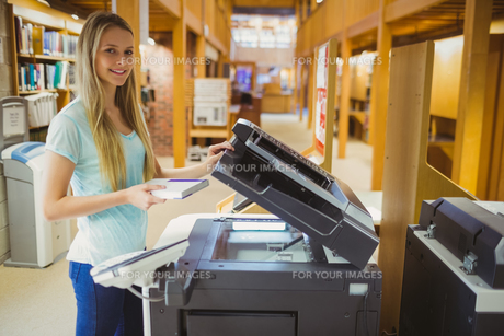 Smiling blonde student making a copyの写真素材 [FYI00010296]