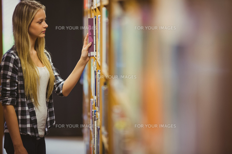 Blonde student reading book next to bookshelfの写真素材 [FYI00010298]