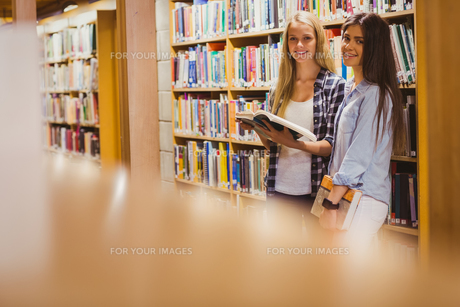 Pretty young students working together with bookの写真素材 [FYI00010313]