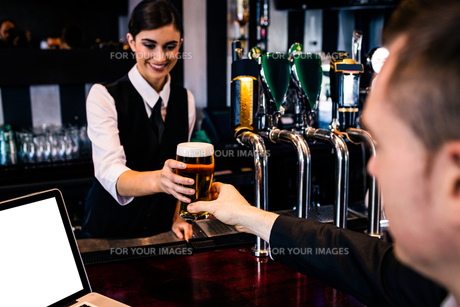 Barmaid serving a pint to customer with laptopの写真素材 [FYI00010380]