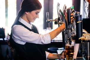 Barmaid serving a pintの写真素材 [FYI00010381]