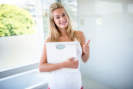 Woman holding a weighting scale with thumbs upの素材 [FYI00010396]