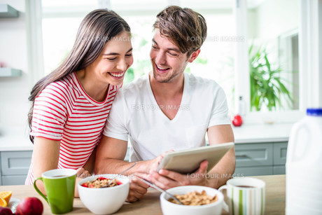 Happy couple using tablet and having breakfastの写真素材 [FYI00010410]