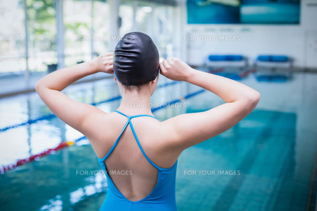 Rear view of fit woman putting on swim capの写真素材 [FYI00010438]