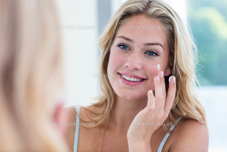 Smiling pretty woman applying cream on her faceの写真素材 [FYI00010464]