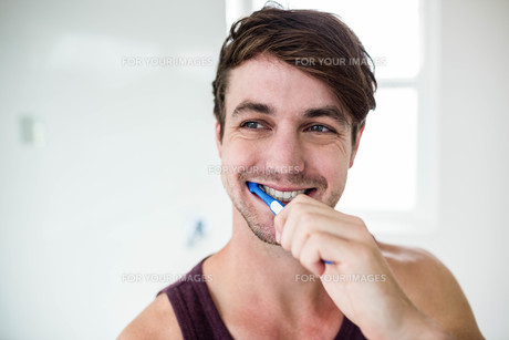 Handsome man cleaning his teethの写真素材 [FYI00010465]