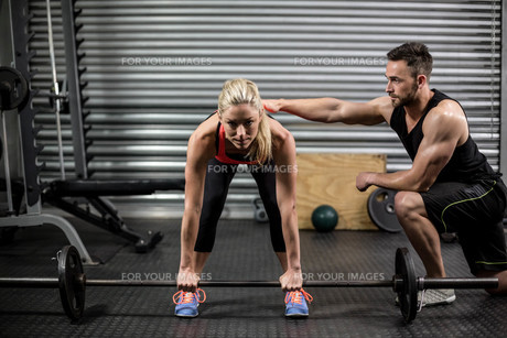 Trainer helping woman with lifting barbellの写真素材 [FYI00010485]