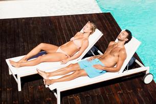 Peaceful couple sunbathing on deck chairsの素材 [FYI00010492]