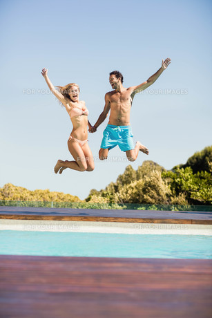 Happy couple jumping in the poolの写真素材 [FYI00010498]
