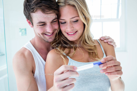 Happy couple looking at pregnancy testの写真素材 [FYI00010504]