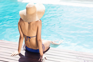 Woman with hat sitting on pools edgeの素材 [FYI00010521]
