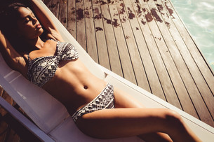 Fit woman lying on deck chairの写真素材 [FYI00010524]