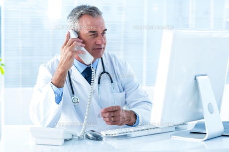 Male doctor holding telephone while looking at computer in hospitalの写真素材 [FYI00010541]