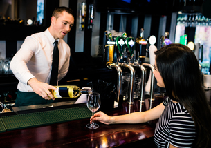 Barman serving a glass of wineの写真素材 [FYI00010544]