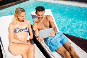 Couple using tablet on deckchairsの写真素材 [FYI00010567]