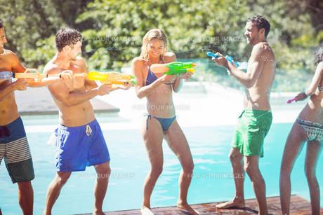 Happy friends doing water gun battleの写真素材 [FYI00010568]