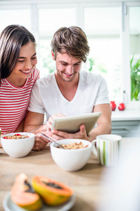 Happy couple using tablet and having breakfastの写真素材 [FYI00010573]