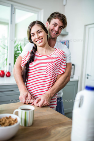 Happy couple standing in kitchenの写真素材 [FYI00010575]