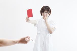 レッドカードを持つ看護師の素材 [FYI00023912]