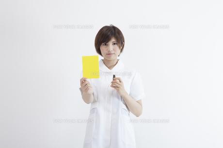 イエローカードを持つ看護師の素材 [FYI00023926]