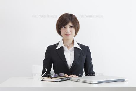 机に座る女性会社員の素材 [FYI00023935]