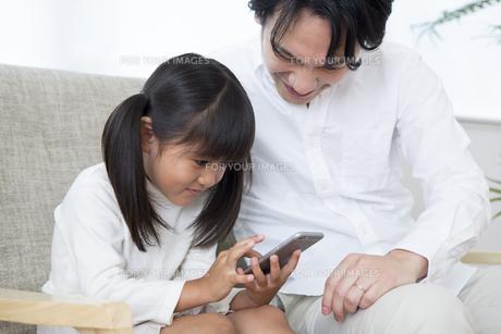 スマホを操作する親子の素材 [FYI00024157]