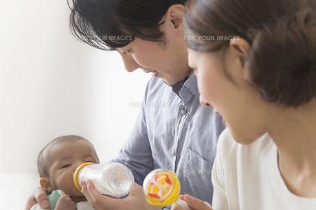 子供にミルクを飲ませる夫婦の素材 [FYI00024212]