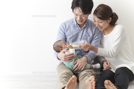 子供にミルクを飲ませる夫婦の素材 [FYI00024289]