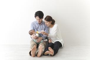 子供にミルクを飲ませる夫婦の素材 [FYI00024299]