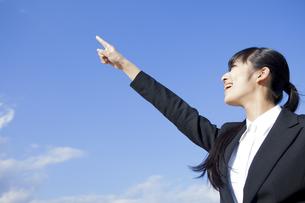空に指を指すビジネスウーマンの素材 [FYI00024563]