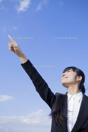 空に指を指すビジネスウーマンの素材 [FYI00024570]