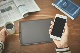 コーヒを飲みながらデバイスとスマートフォンを使う女性の写真素材 [FYI00024942]