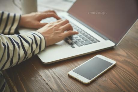 カフェでパソコンとスマートフォンを使う女性の写真素材 [FYI00024949]