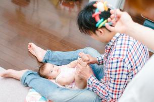 パパが赤ちゃんをあやす姿をみつめながらママもおもちゃであやしてる姿の素材 [FYI00024960]