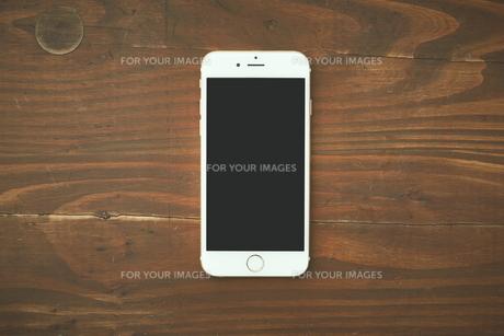 木の天板に置いてあるスマートフォンの写真素材 [FYI00024961]