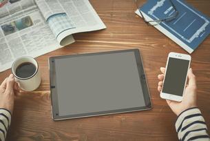 コーヒを飲みながらデバイスとスマートフォンを使う女性の写真素材 [FYI00024963]