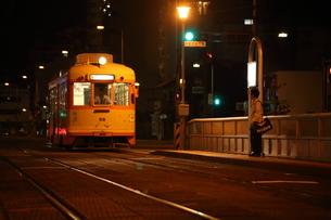 夜間に走る路面電車と駅で待つ人の素材 [FYI00024988]