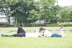 芝生で寝ころび見つめあうカップルの写真素材 [FYI00024999]
