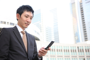 携帯を見るビジネスマンの写真素材 [FYI00032751]
