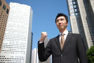 青空の下でガッツポーズをするビジネスマンの写真素材 [FYI00032775]