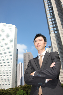 青空の下で腕を組むビジネスマンの写真素材 [FYI00032779]