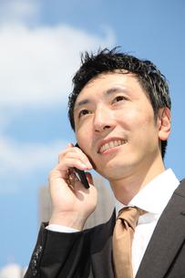 青空の下で電話するビジネスマンの写真素材 [FYI00032781]
