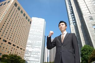 青空の下でガッツポーズをするビジネスマンの写真素材 [FYI00032783]