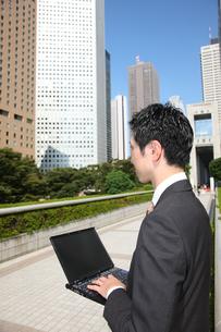 オフィス街でパソコン操作するビジネスマンの写真素材 [FYI00032788]