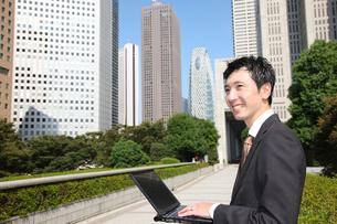 オフィス街でパソコン操作するビジネスマンの写真素材 [FYI00032789]