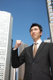 青空の下でガッツポーズをするビジネスマンの写真素材 [FYI00032793]