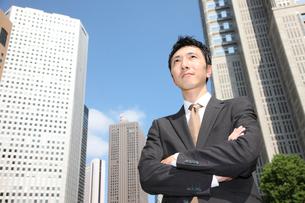 青空の下で腕を組むビジネスマンの写真素材 [FYI00032801]